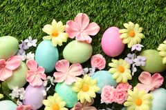 Colorful Easter eggs on grass with flowers. Background Royalty Free Stock Photos