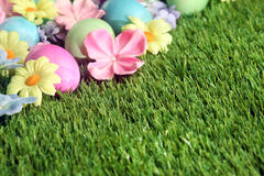 Colorful Easter eggs on grass with flowers Stock Photo