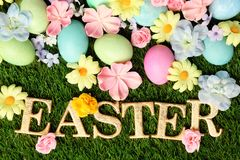 Colorful Easter eggs on grass with flowers. Background Stock Photos