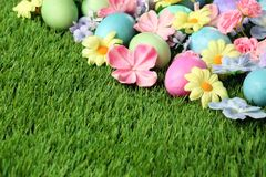 Colorful Easter eggs on grass with flowers. Background Royalty Free Stock Photo