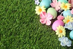 Colorful Easter eggs on grass with flowers. Background Royalty Free Stock Images