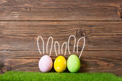 Colorful Easter eggs on grass with painted rabbit ears on wooden background.  Stock Photos