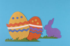 Colorful easter eggs with grass and rabbit. Colorful eggs with grass and rabbits drawn and cut on paper, easter egg on a blue background stock photography