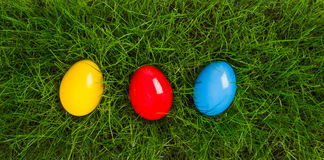 Colorful easter eggs in grass. Easter eggs in yellow, red and blue lying in grass in birds eye view Stock Images