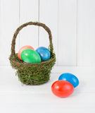 Colorful Easter eggs in green basket on wooden background Royalty Free Stock Photos