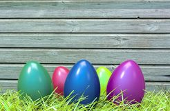 Colorful Easter eggs in green grass and wooden plank. In background. 3D illustration and rendering Stock Photos