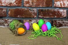 Colorful Easter eggs in a green paper nest and glass jar on a red old brick background Royalty Free Stock Photography