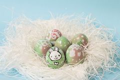 Decorated easter eggs. Colorful Easter eggs handpainted with floral decoration and a bunny, on a white nest. Pastel blue background. Perfect for your festive Stock Image