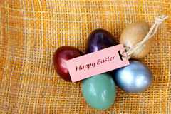 Colorful easter eggs with Happy Easter paper tag on bamboo weave. Royalty Free Stock Photos