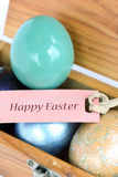 Colorful easter eggs with Happy Easter text paper tag. Royalty Free Stock Photography