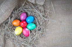 Colorful easter eggs in hay on sackcloth backround Royalty Free Stock Photography