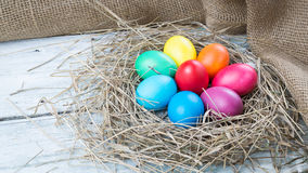 Colorful easter eggs in hay on wooden background Stock Images