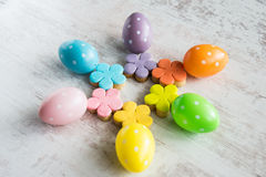 Colorful easter eggs and homemade fondant covered flower cookies on a white wood background Royalty Free Stock Images