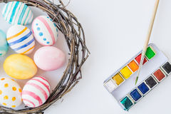 Colorful Easter Eggs isolated on the white background with nest and wreath and watercolor paint and brush. Selective Stock Photo