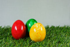 Colorful easter eggs. On a lawn of artificial green stock photo