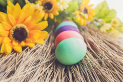 Colorful Easter eggs laying on a straw. With some yellow flowers stock image
