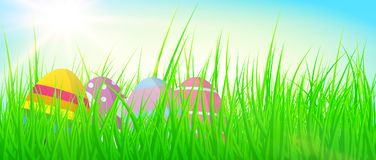 Colorful easter eggs in lush green grass against blue sky. Colorful easter eggs in fresh green grass against blue sky Royalty Free Stock Image