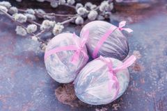 Colorful Easter eggs lying on a beautiful vintage background with bouquet made of willow branches. The view from the top royalty free stock image