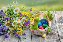 Colorful Easter eggs lying on the plate in the form of a chicken on a wooden background with a bouquet of wild flowers daisies and royalty free stock photography