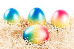 Colorful easter eggs lying on some hay Stock Images