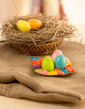 Colorful Easter eggs lying on table covered with burlap Stock Photo
