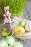 Colorful Easter eggs lying on the table next to the green of fresh grass and the white rabbit Stock Image