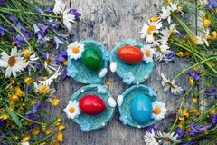 Colorful Easter eggs lying on the wicker plates in the form of a nest on wooden background with a bouquet of wild Royalty Free Stock Photo