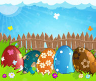 Colorful Easter eggs near a wooden fence in the meadow Royalty Free Stock Image