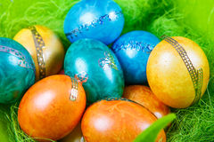 Colorful easter eggs in nest as traditional detail of Easter hol Stock Photos