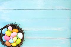 Colorful Easter eggs in nest on blue wooden background. royalty free stock image