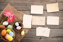 Colorful Easter eggs in nest with flower and empty old paper photo album on wood table Stock Image