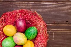 Colorful easter eggs in nest on wooden background. Eggs handmade new style of colouring . Pattern, easter concept Royalty Free Stock Photos