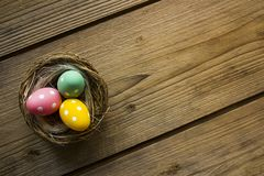 Colorful easter eggs in nest on wooden table stock photo