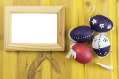 Colorful Easter eggs on an old yellow wooden background. Celebrating Easter holidays.  Symbol of Easter. Stock Photos