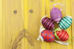 Colorful Easter eggs on an old yellow wooden background. Celebrating Easter holidays.  Symbol of Easter. Stock Images