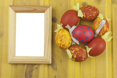 Colorful Easter eggs on an old yellow wooden background. Celebrating Easter holidays.  Symbol of Easter. Royalty Free Stock Images