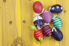 Colorful Easter eggs on an old yellow wooden background. Celebrating Easter holidays.  Symbol of Easter. Stock Photography
