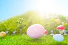 Colorful easter eggs and one big pink easter egg on spring green grass.  Royalty Free Stock Images