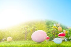 Colorful easter eggs and one big pink easter egg on spring green grass.  Stock Photo
