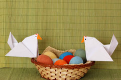 Colorful Easter eggs. And origami hens in a small basket Royalty Free Stock Image