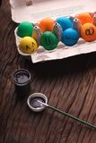 Colorful Easter eggs with painted face in egg carton box and near paint with a brush on wooden table. Funny faces royalty free stock photography