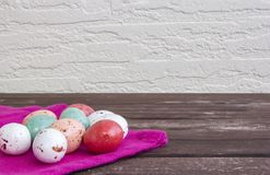 Colorful Easter eggs on a pink napkin / tablecloth on a brown wooden table and white wall. stock photos