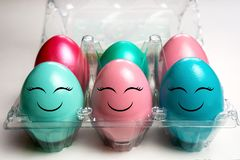 Colorful easter eggs in plastic egg case pack with happy emoji faces stock image