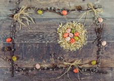 Colorful Easter Eggs with pussy-willow Decorated on Wooden Background. Chocolate colored eggs in the nest of sawdust, decorated frame of pussy-willow, bows of Stock Photo