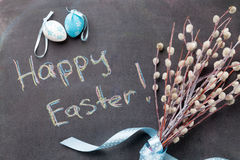 Colorful easter eggs and pussy willow. Over blackboard with greetings Royalty Free Stock Photo