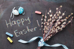 Colorful easter eggs and pussy willow. Over blackboard with greetings Royalty Free Stock Photos