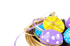Colorful easter eggs with ribbons. In basket isolated on white background Stock Images