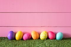 Colorful Easter Eggs in Row on Bottom of Pink Wood Boards Wall Background and Laying in Green Grass with room or space for copy