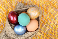 Colorful easter eggs in sack bag on weave background Stock Photos