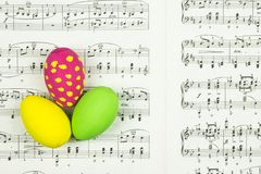 Colorful Easter eggs on sheet with classic music notes as background. Three colorful painted Easter eggs standing on sheet with classic music notes pages as stock photo